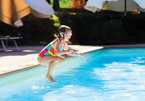 Young girl jumping in the pool